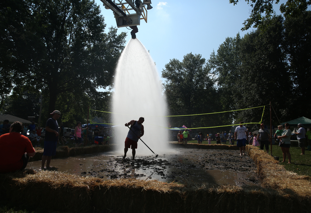 Auburn volunteer firefighter Andy Carrigan stands under a shower of water from a firetruck aerial ladder while using a rake to prepare the mud volleyball court for tournament play in Union Park Saturday morning. David Spencer/The State Journal-Register
