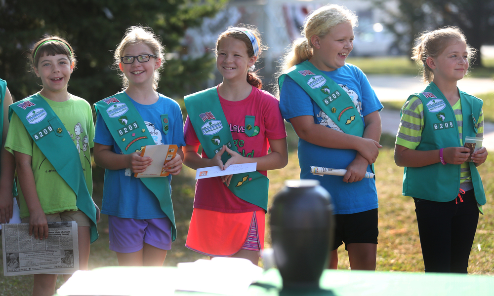 Members of Girl Scout Troop #6209 each hold an item they would soon place in a time capsule urn, seen in foreground, that would soon be buried in Community Park on the village square early Saturday morning. The capsule is scheduled to be opened on Sept. 5, 2065.  David Spencer/The State Journal-Register