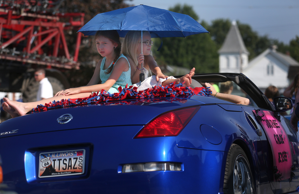 Area royalty assembled off the village square before riding in the parade. Little Miss Auburn contestants Chloe Allers, 8 at left is joined by fellow Little Miss Journee Jackson, 6 on the back of a car while they shield themselves from the sun using an umbrella. Also riding up front was Tiny class Auburn contestant Jersee Jackson, 4. David Spencer/The State Journal-Register
