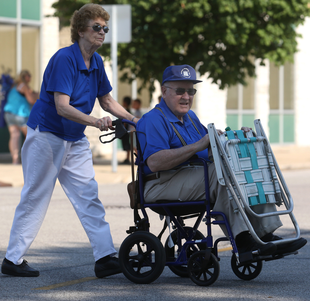 Married 57 years, Sue Walker of Auburn pushes her husband Tom Walker while making their way to a prime seat along the parade route on the village square Saturday morning. David Spencer/The State Journal-Register