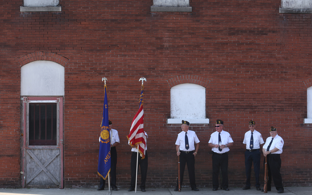 Auburn VFW post 8157 and American Legion post 277 Color Guard members find some shade next to a building off the village square before marching in the parade. David Spencer/The State Journal-Register