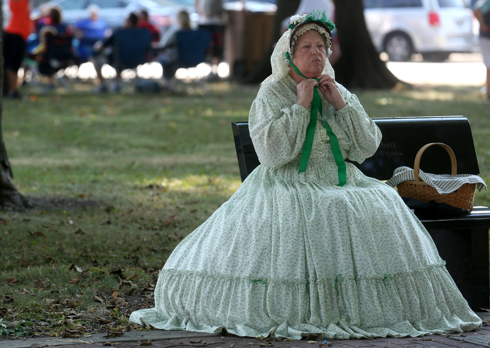 Mary Todd Lincoln presenter Carol Simpkins of Heyworth ties her bonnet while seated in the shade on the village square before the start of the parade. David Spencer/The State Journal-Register
