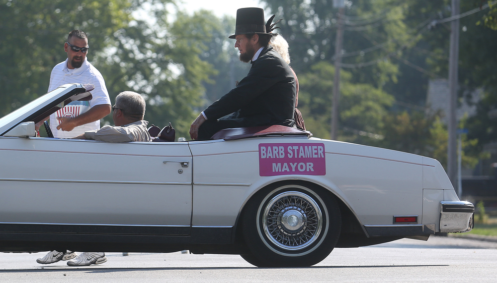 Abraham Lincoln-Gary Simpkins of Heyworth- rides along with Auburn Mayor Barb Stamer in the parade along N. Fifth Street Saturday morning.  David Spencer/The State Journal-Register
