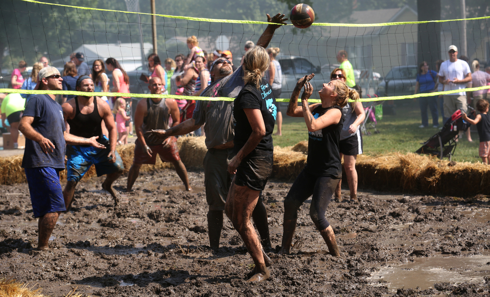 "Mud volleyball teams ""We Showed Up"" at left and ""Old School"" competed during tournament play at Union Park Saturday morning. Organizers said the process to build the court started this past Tuesday and involved bringing in an additional five tons of dirt, with thousands of gallons of water delivered to the mix courtesy of an Auburn Volunteer Fire Department aerial truck. David Spencer/The State Journal-Register"