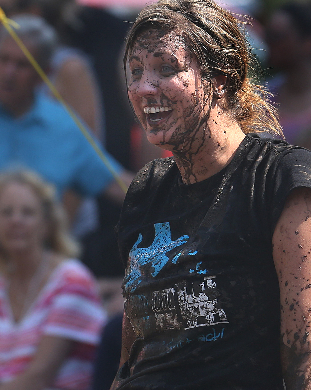"Mud volleyball team ""Old School"" member Danielle Devos shows off her pearly whites while her face is splattered with mud between a service volley during tournament play at Union Park Saturday morning. Organizers said the process to build the court started this past Tuesday and involved bringing in an additional five tons of dirt, with thousands of gallons of water delivered to the mix courtesy of an Auburn Volunteer Fire Department aerial truck. David Spencer/The State Journal-Register"