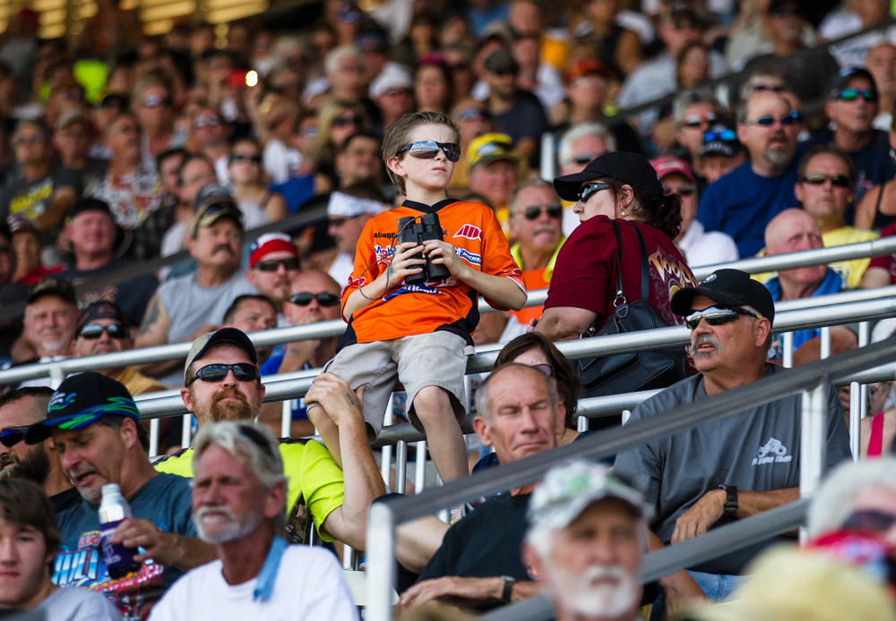 Braden Mueller, 10, of Chapin, ill., takes in the heat races with a set of binoculars from a packed Grandstand during the AMA Pro Flat Track Grand National Championship Springfield Mile II at the Illinois State Fairgrounds, Sunday, Sept. 6, 2015, in Springfield, Ill. Justin L. Fowler/The State Journal-Register