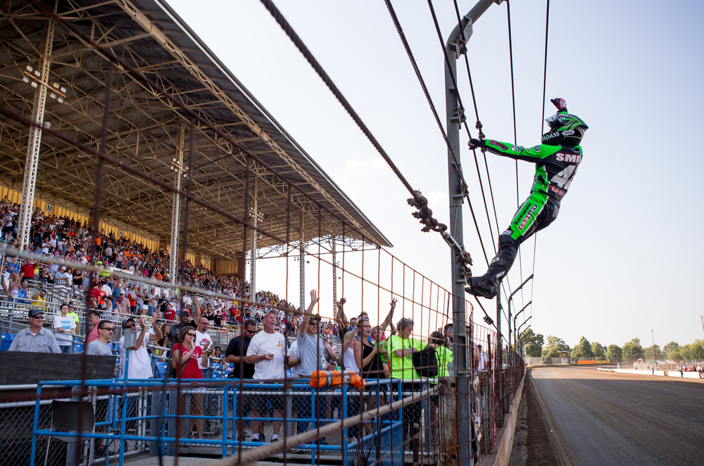 Bryan Smith climbs the fence to celebrate his sixth win at the AMA Pro Flat Track Grand National Championship Springfield Mile II at the Illinois State Fairgrounds, Sunday, Sept. 6, 2015, in Springfield, Ill. Justin L. Fowler/The State Journal-Register