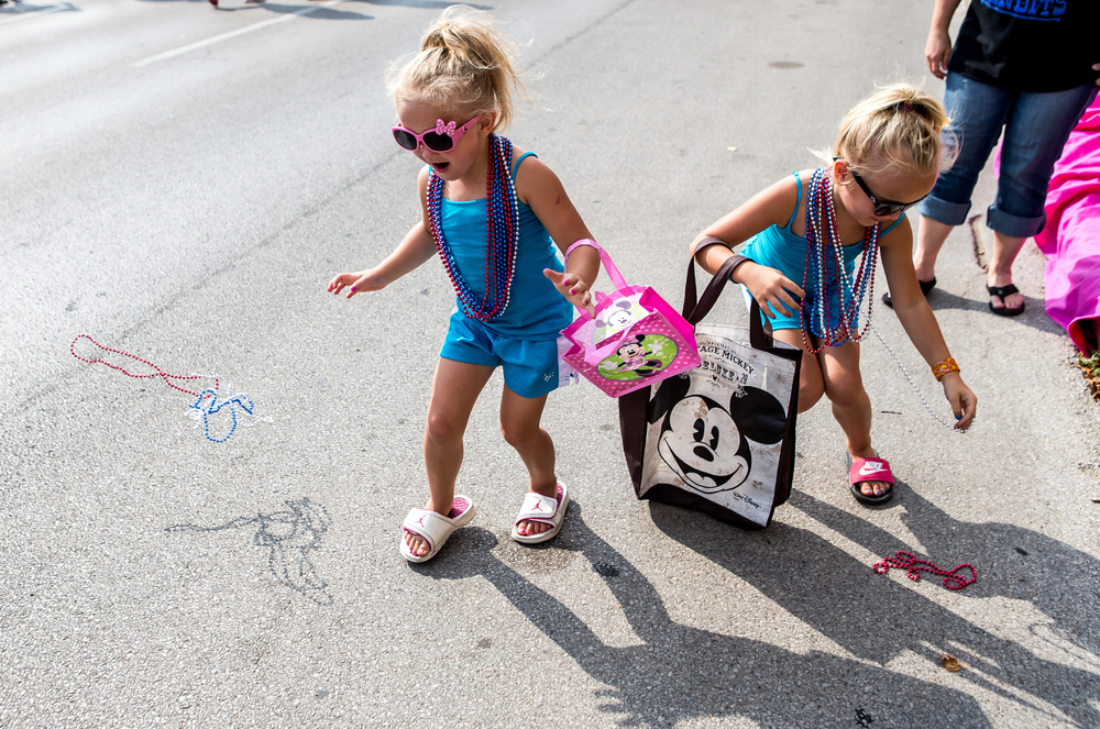Jersee Jackson, 4, left, and her sister Journee Jackson, 6, right, go for beads being thrown out by Plumbers and Steamfitters Local #137 during the annual Labor Day Parade, Monday, Sept. 7, 2015, in Springfield, Ill. Justin L. Fowler/The State Journal-Register