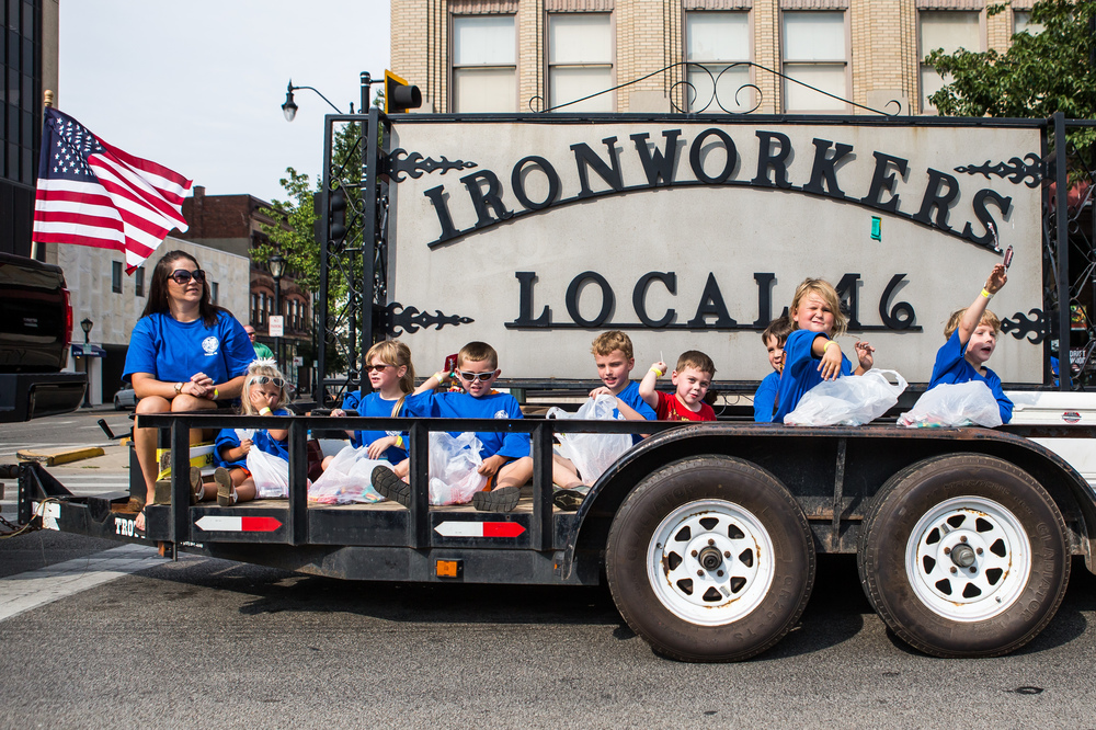 Children on the Ironworkers Local #46 float toss out candy as they march down Fifth Street during the annual Labor Day Parade, Monday, Sept. 7, 2015, in Springfield, Ill. Justin L. Fowler/The State Journal-Register