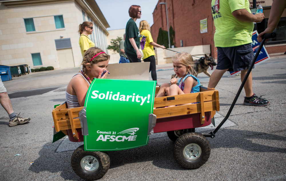 Ainsley Kerns, 6, left, and her sister, Fiona, 4, enjoy the their candy towards the end of the parade with AFSCME Council 31 during the annual Labor Day Parade, Monday, Sept. 7, 2015, in Springfield, Ill. Justin L. Fowler/The State Journal-Register