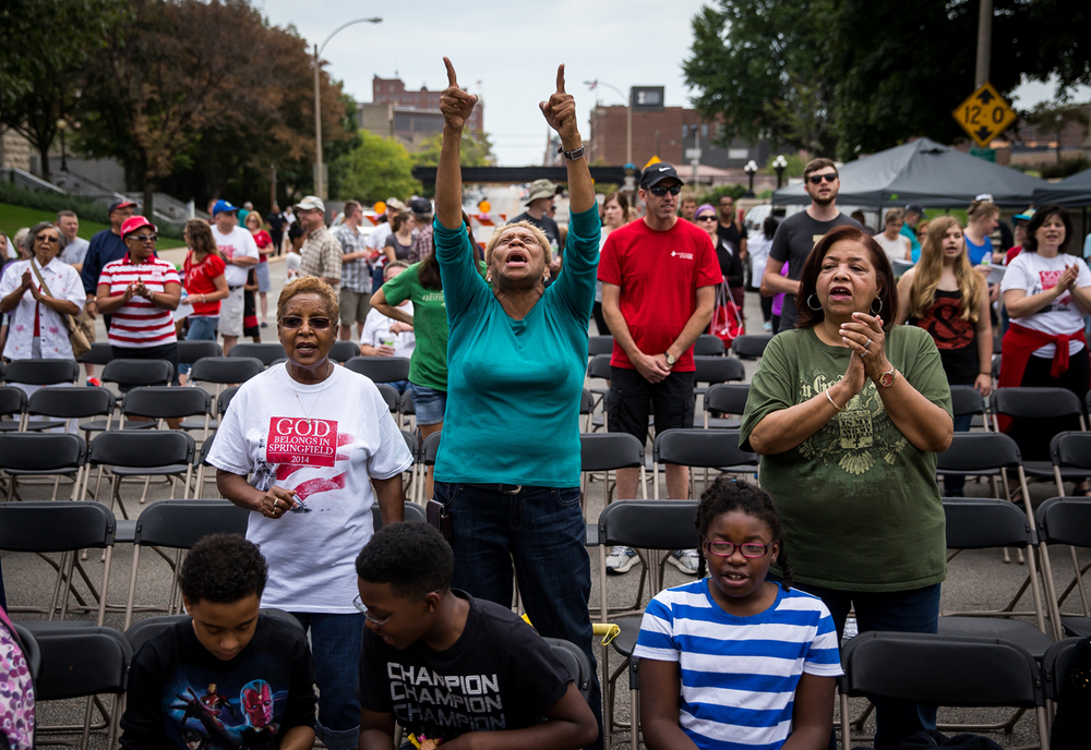 Helen Williams, center, a member of Abundant Faith Christian Center, worships along with a musical performance during the Abraham Lincoln Prayer Walk at the intersection of 2nd Street and Capitol Avenue, Saturday, Aug. 29, 2015, in Springfield, Ill. Participants marched from Comer Cox Park to Illinois State Capitol for the praise and worship event. Justin L. Fowler/The State Journal-Register
