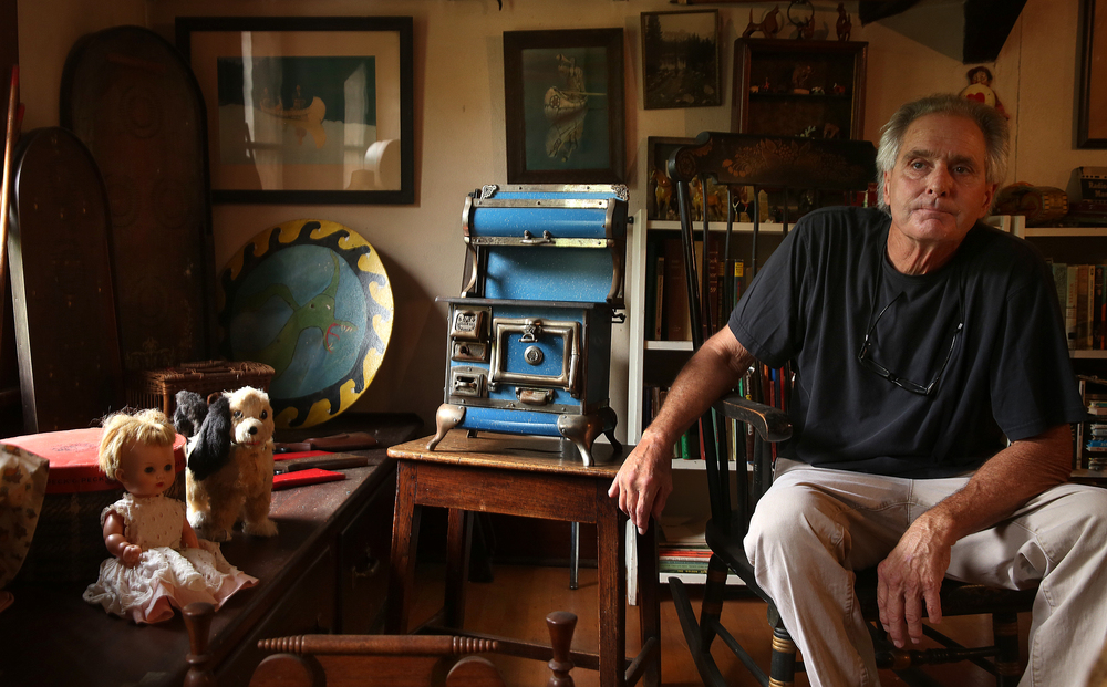 Bob Pasquesi sits in the attic playroom of the main house on Tuesday, Sept. 8, 2015 with an early 1900's blue enameled Karr Range Co. stove made in Belleville, Ill that is one of hundreds of toys to be auctioned. David Spencer/The State Journal-Register
