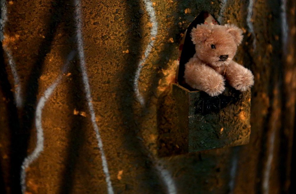 A Steiff teddy bear peaks out from a log doll house seen in the attic playroom on Tuesday, Sept. 8, 2015 and will be auctioned this month. David Spencer/The State Journal-Register