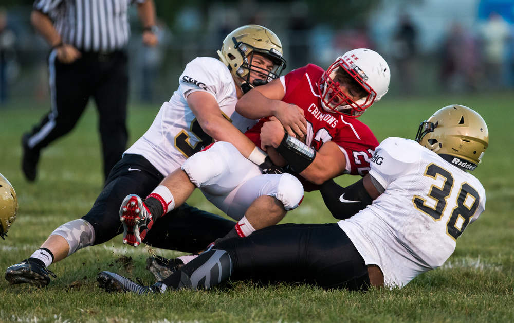 Sacred Heart-Griffin's DJ Mackey (38) and Lance Winkler (56) combine to bring down Jacksonville's Matt Rooney (22) on a rush during the first half at Kraushaar-Rosenberger Field, Friday, Sept. 11, 2015, in Jacksonville, Ill. Justin L. Fowler/The State Journal-Register