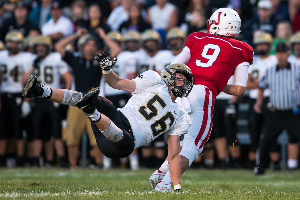 Jacksonville's Joe Brannan (9) spins out of a sack from Sacred Heart-Griffin's Lance Winkler (56) during the first half at Kraushaar-Rosenberger Field, Friday, Sept. 11, 2015, in Jacksonville, Ill. Justin L. Fowler/The State Journal-Register