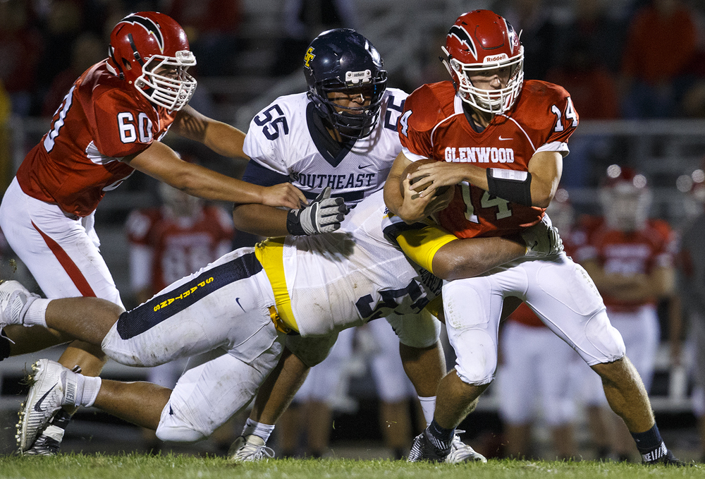 Southeast's Kamarcus Tucker wraps up Glenwood quarterback Cole Hembrough at Glenwood High School Friday, Sept. 11, 2015. Ted Schurter/The State Journal-Register