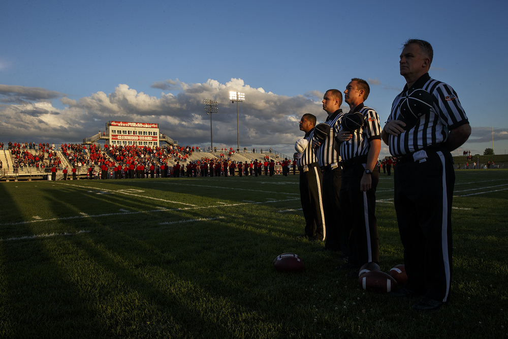 IHSA game officials face the flag for the playing of the national anthem before Glenwood hosted Southeastl Friday, Sept. 11, 2015. Ted Schurter/The State Journal-Register