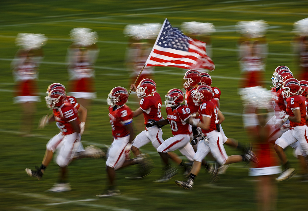 Glenwood's Ethan Brill runs the American flag onto the field as the Titans prepare to face Southeast at Glenwood High School Friday, Sept. 11, 2015. Ted Schurter/The State Journal-Register