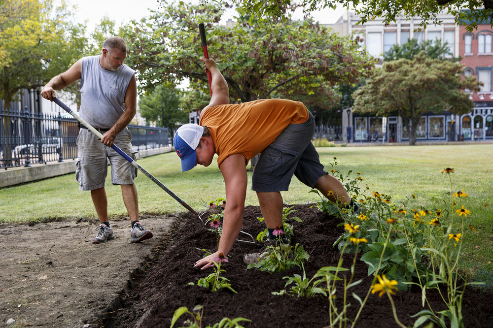 Dan Pappas, left, and Blain Carr of CopperTree Outdoor Lifestyles mulch the purple coneflowers and black-eyed susans they planted in a plot on the south side of the Old State Capitol Thursday, Sept. 10, 2015. The work is a sample of the firm's proposed recreation of a Lincoln-era strolling path around the perimeter of the Old State Capitol. The project will also includes trees, longshadow planters and benches. The Old State Capitol Foundation is hosting a fundraiser for the project, Canapés at the Capitol, on September 12, 2015. Tickets are one for $100, two for $150 and additional tickets are $50 each. Ted Schurter/The State Journal-Register