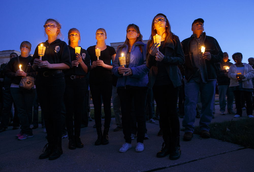 Members of the Minier Police Explorers joined about 200 people in a candlelight vigil around the Illinois Police Officers Memorial Saturday, Sept. 12, 2015. Event organizers created the event in honor of slain Harris County Texas Deputy Darren Goforth and all of the other men and women who work in law enforcement. Ted Schurter/The State Journal-Register