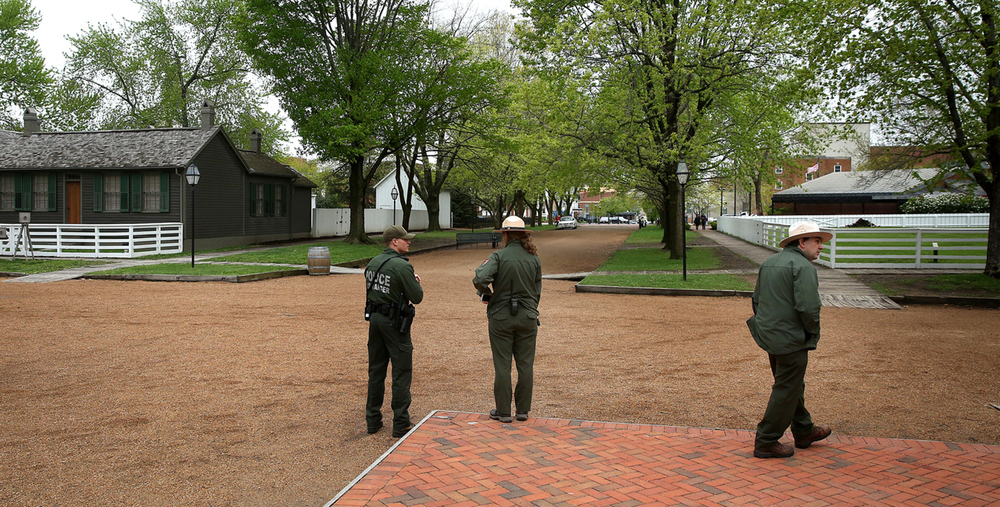 From a similar vantage point now, National Park Service rangers and a police officer stand on the sidewalk in front of the Lincoln Home. The Corneau House is across the street to the left. David Spencer/The State Journal-Register