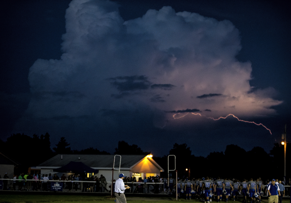 A lightning bolt streaks through the sky as players for Auburn and North Mac head for the locker rooms for a weather delay with 2:41 left in the first quarter at Michael J. Potts Memorial Field, Friday, Sept. 18, 2015, in Auburn, Ill. Justin L. Fowler/The State Journal-Register