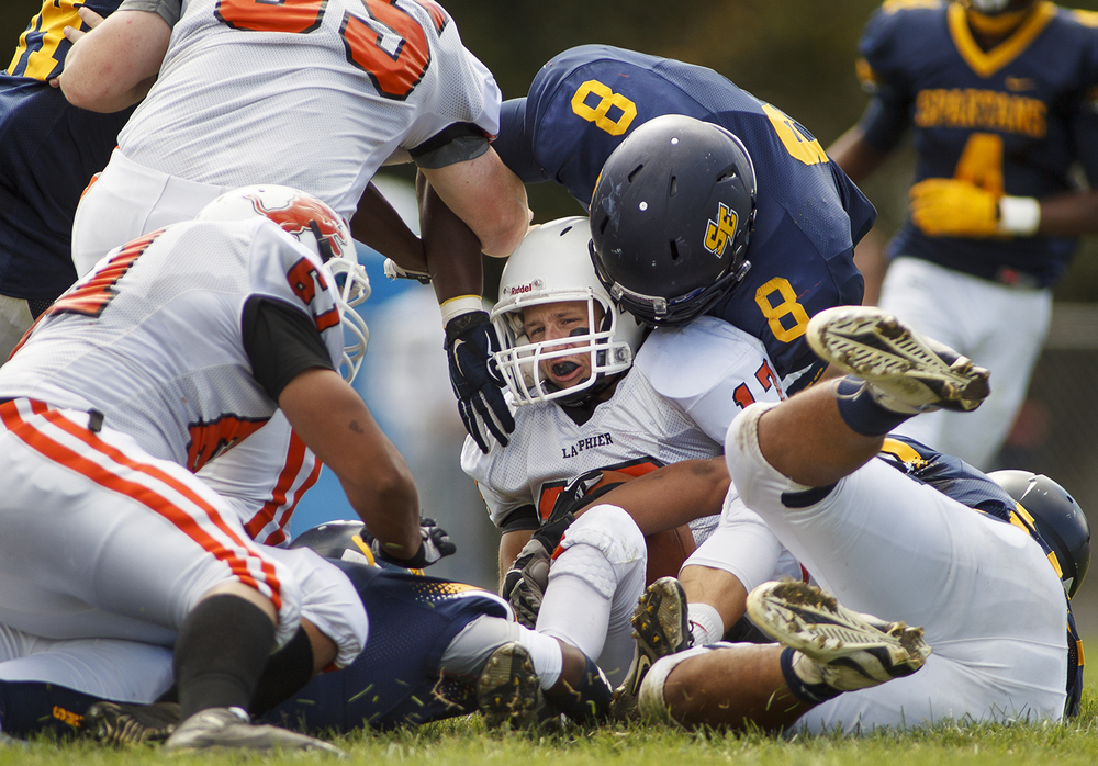 Lanphier's quarterback Joseph Varela is brought down by a handful of Southeast defenders at Southeast High School Saturday, Sept. 19, 2015. Ted Schurter/The State Journal-Register