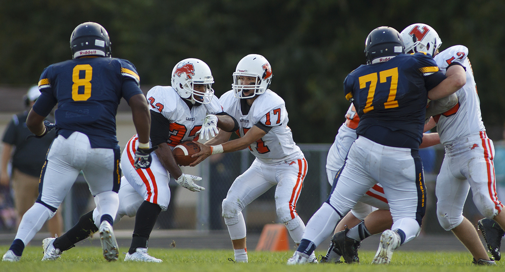 Lanphier's Reggie Dickerson takes a handoff from quarterback Joe Varela at Southeast High School Saturday, Sept. 19, 2015. Ted Schurter/The State Journal-Register