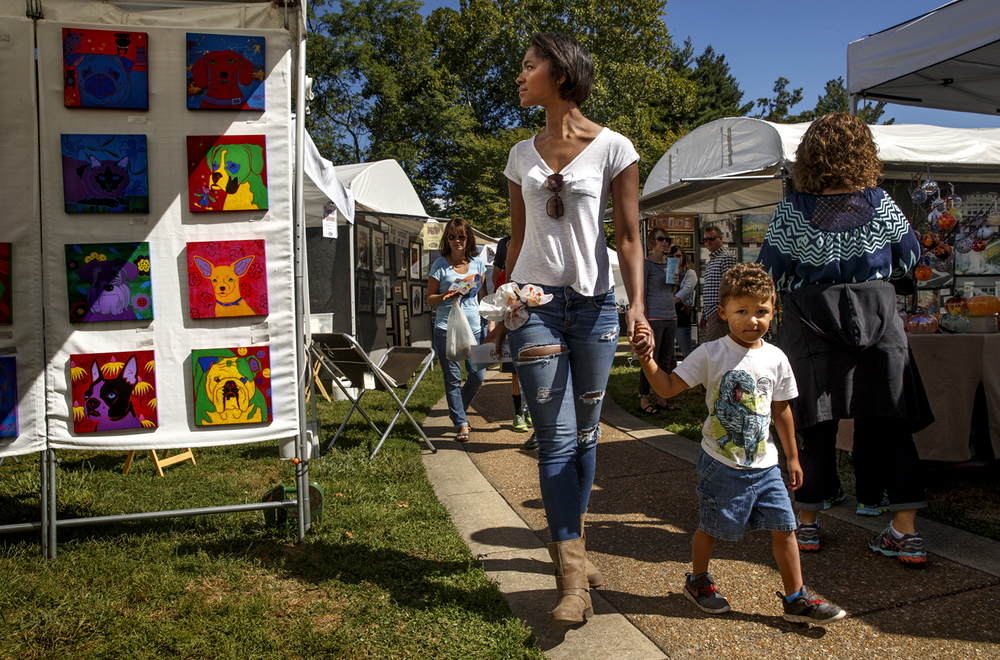 A guest glances at the Neo Pop paintings by Atlanta artist Angela Bond at Art Spectacular at Washington Park Sunday, Sept. 13, 2015. The festival featured 50 artists and artisans, music and children's programs. Ted Schurter/The State Journal-Register