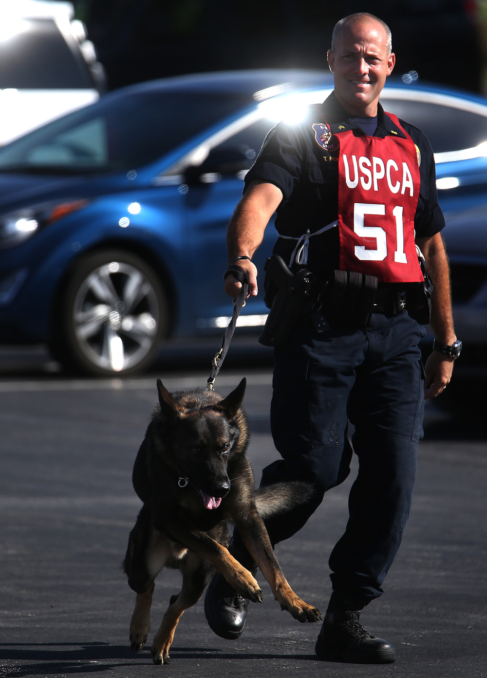 "Baton Rouge K-9 police officer Tom Ricken's German Shepard ""Zorro"" leads the way in route to competing on the obstacle course at LLCC Tuesday. David Spencer/The State Journal-Register"