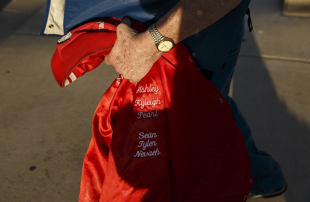 Eldon Eck carries his jacket that bears the names of many of his more than 3 dozen grandchildren and great-grandchildren to the Rochester Southeast game at Rochester High School Friday Sept. 25, 2015. One of his granddaughters was cheering for the Rockets. Ted Schurter/The State Journal-Register