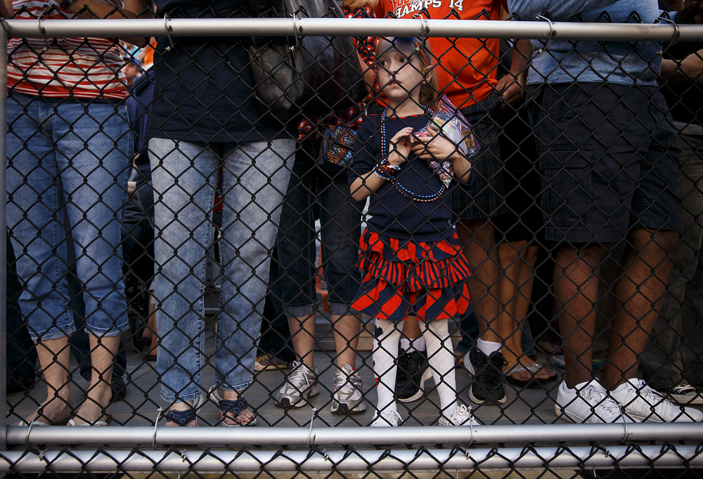 Maley Kindred watches her big sister sing the National Anthem with other third graders before the Rocket's face Southeast at Rochester High School Friday Sept. 25, 2015. Ted Schurter/The State Journal-Register