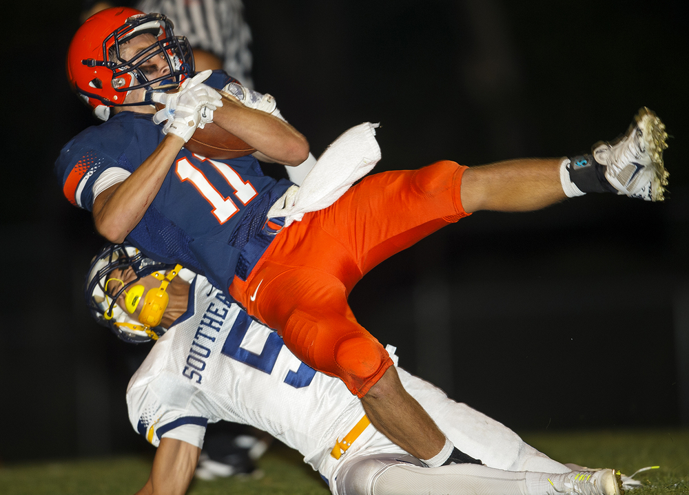 Southeast's Adrian Greene brings down Rochester's Collin Etherton at Rochester High School Friday Sept. 25, 2015. Ted Schurter/The State Journal-Register