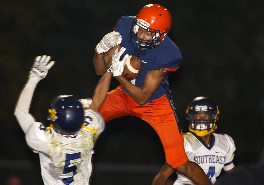 Rochester's Collin Stallworth makes a leaping catch over Southeast's Adrian Greene at Rochester High School Friday Sept. 25, 2015. Ted Schurter/The State Journal-Register