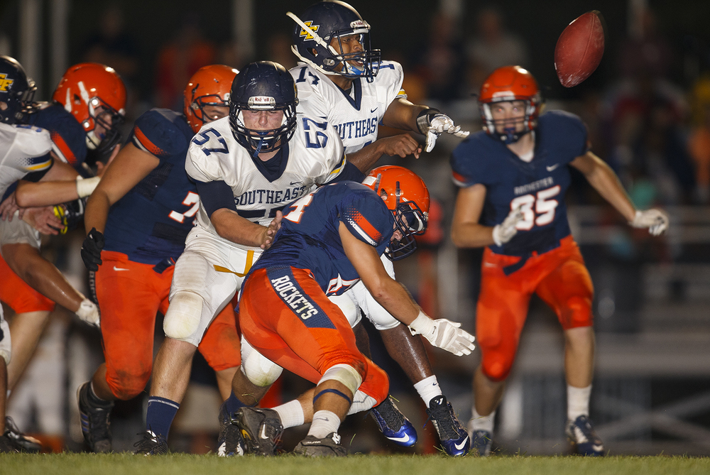 Southeast's Isaiah Timms tries to flip the ball back to Eddie Gailes as the Rochester defense closes in at Rochester High School Friday Sept. 25, 2015. Ted Schurter/The State Journal-Register