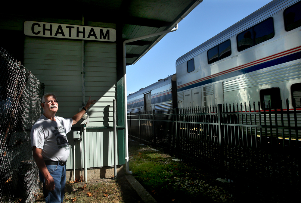 Chatham Railroad Museum Association President Bill Shannon waves to a northbound Amtrak train passing the Chatham Depot on Wednesday, Sept. 23, 2015. Chatham Depot Day, a fundraising event for the historic Chatham Depot & Railroad Museum which hopes to replace the roof of the structure and to put a new coat of paint on the outside, will be held at the depot on Sunday Oct. 4 from 1 pm to 5 pm. Originally built in 1902 by the Chicago & Alton Railroad as a passenger and freight station and owned by the village of Chatham, the depot today is overseen by the non-profit Chatham Railroad Museum Association.  David Spencer/The State Journal-Register