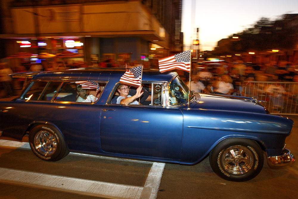 Kathy Mull waves from the front seat of the 1955 Chevrolet Nomad that belongs to her and her husband, Wesley, as they cruise through the intersection of Sixth and Monroe streets Friday, Sept. 25, 2015, as part of the Route 66 Mother Road Festival. In the backseat is their granddaughter, Evelyn Mull. The Mulls, who are from Carol Stream, Ill., have been to the festival nine times. Rich Saal/The Strate Journal-Register