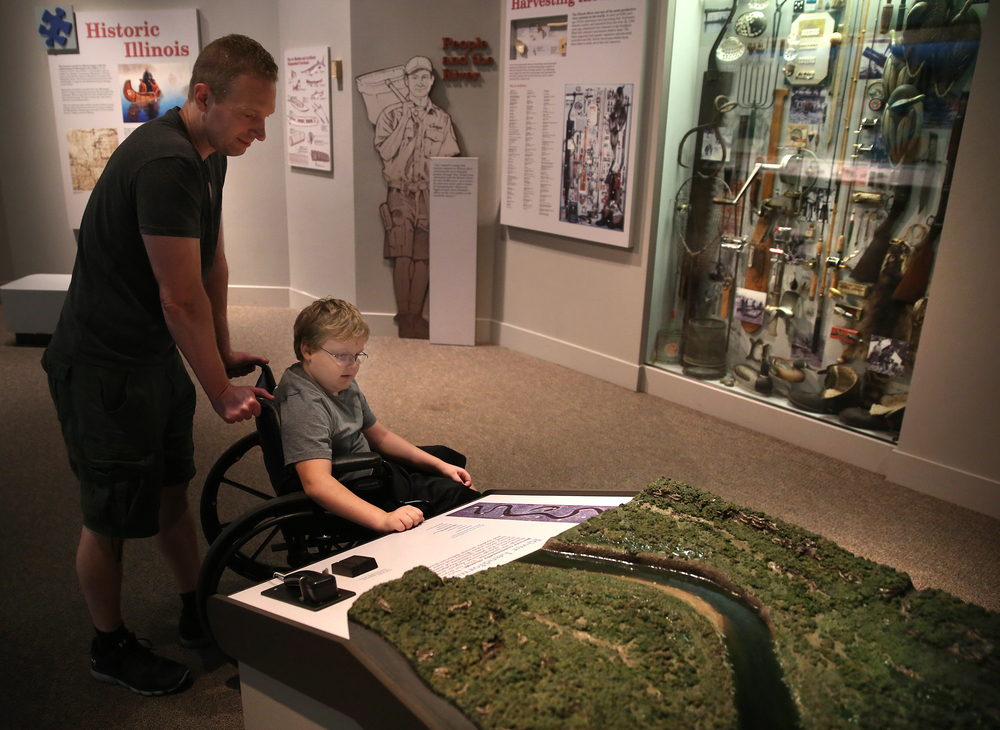 John Alt of Springfield and son Isaac Alt examine a model of a river landform in the first floor natural history display area on Wednesday. David Spencer/The State Journal-Register