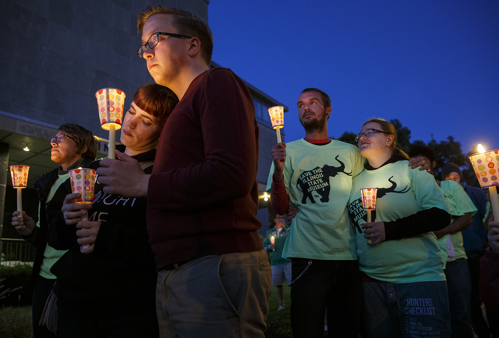 Tomi Mick leans on Keith Harms as they listen to speakers during a candlelight protest in front of the Illinois State Museum in Springfield, Ill., Thursday Oct. 1, 2015. Ted Schurter/The State Journal-Register