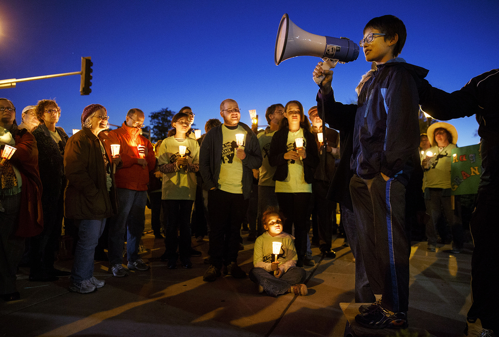 """Locking all the stuff up in this museum away from the public is just a bad idea,"" 11-year-old Max Kattner told a crowd of about 100 people gathered for a candlelight protest in front of the Illinois State Museum in Springfield, Ill., Thursday Oct. 1, 2015. ""People will not know about our cultural and natural history."" Gov. Bruce Rauner's administration initially planned to close the museum Wednesday and lay off all but three of its staff members. The museum closed to the public Thursday but the American Federation of State, County and Municipal Employees, which represents most of the museum employees still on the job, is challenging the layoffs in court, saying they did not comply with the union's labor contract."