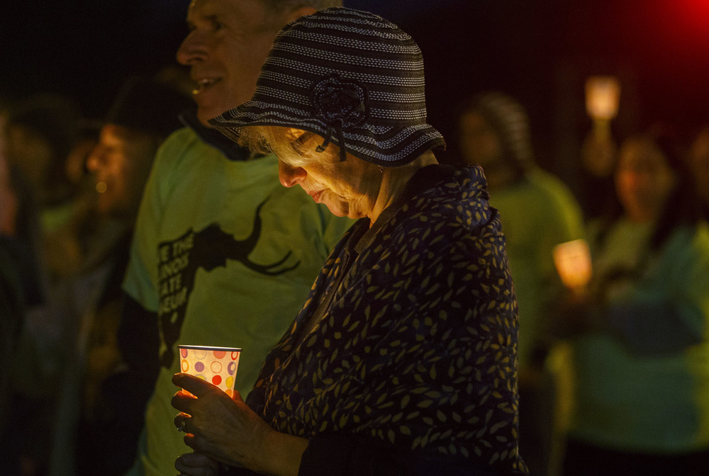 Judy Hild, a member of the Raging Grannies International, attends a candlelight protest in front of the Illinois State Museum in Springfield, Ill., Thursday Oct. 1, 2015. Ted Schurter/The State Journal-Register