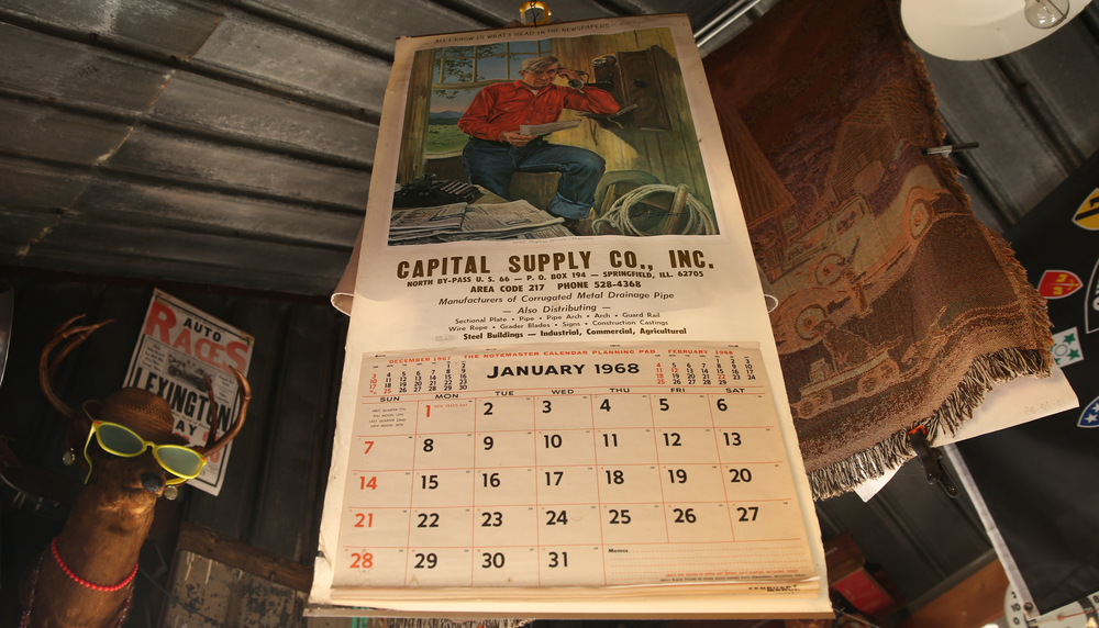 "Artwork of Will Rogers speaking into a wall telephone with the quote ""All I know is what I read in the newspapers"" and used for a vintage 1968 Capital Supply Co. of Springfield calendar hangs from the ceiling inside the former Mahan's filling station on the museum property seen Thursday, Oct. 1, 2015. David Spencer/The State Journal-Register"