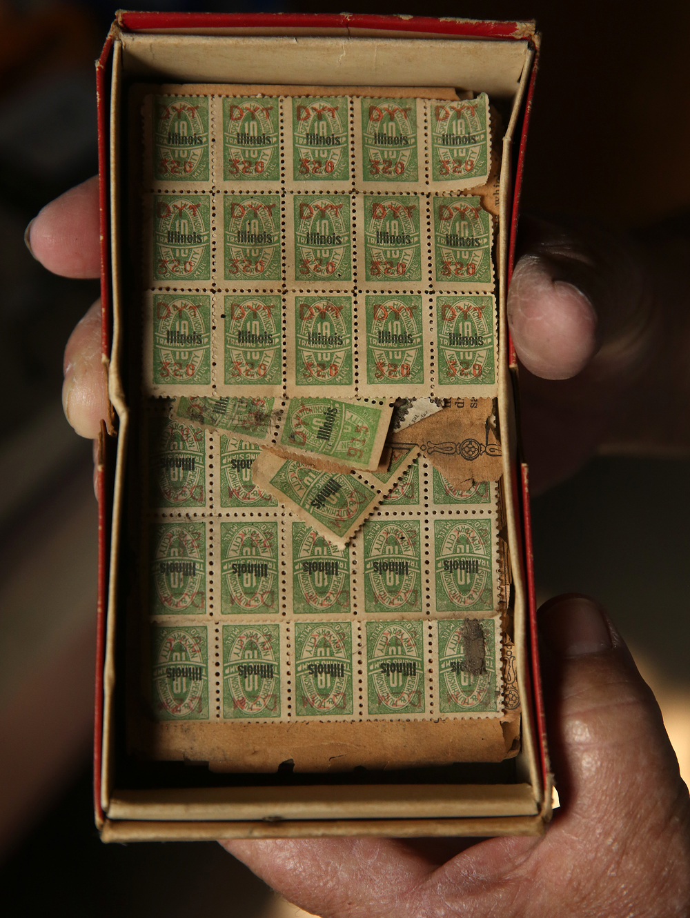 Rare S&H Green Stamps from 1916 (Sperry & Hutchinson first issued them in 1912) are held by Bill Shea Jr. in the main museum on Thursday, Oct. 1, 2015. David Spencer/The State Journal-Register
