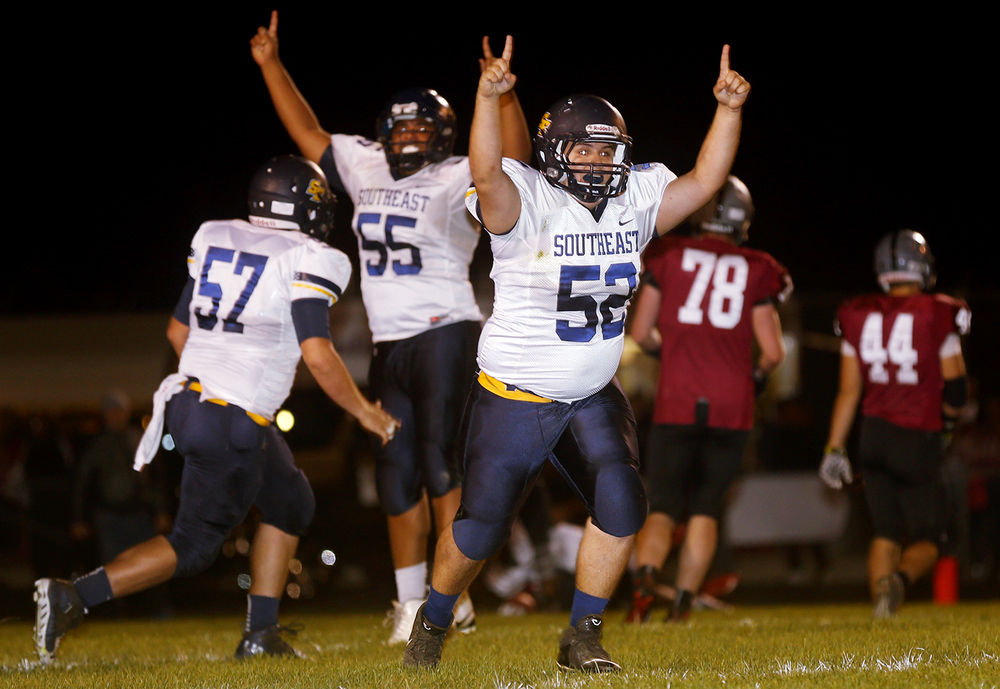 Southeast's Colton Simpson (57), Laquan Price (55) and Chris Brown (52) celebrate after Tae Smith caught a bobbled two-point conversion attempt to put the Spartans ahead of Springfield at the end of the first half at Memorial Stadium Friday, Oct. 2, 2015. Ted Schurter/The State Journal-Register