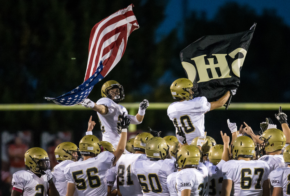 Sacred Heart-Griffin's Devin Thomas (22) and Jake Reid (10) wave their flags on the shoulders of their teammates as they take the field to take on Glenwood at Glenwood High School, Friday, Oct. 2, 2015, in Chatham, Ill. Justin L. Fowler/The State Journal-Register