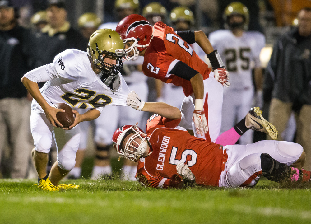 Glenwood's Clark Gaden (5) pulls down Sacred Heart-Griffin's Colin Boyd (29) after a botched extra point in the fist half at Glenwood High School, Friday, Oct. 2, 2015, in Chatham, Ill. Justin L. Fowler/The State Journal-Register