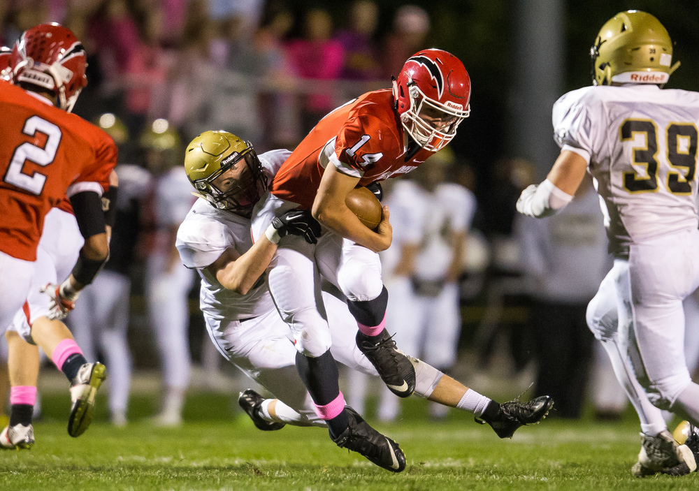 Glenwood's Cole Hembrough (14) is brought down by Sacred Heart-Griffin's Lance Winkler (56) on a rush in the fist half at Glenwood High School, Friday, Oct. 2, 2015, in Chatham, Ill. Justin L. Fowler/The State Journal-Register