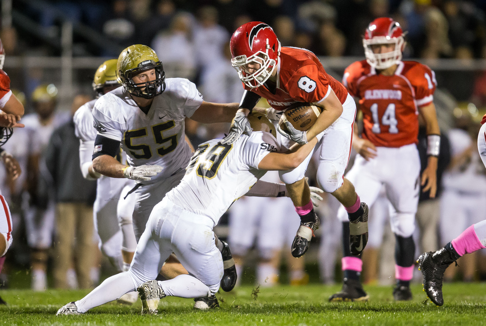 Glenwood's Brandon Hay (8) tries to jump out of a tackle from Sacred Heart-Griffin's Luke Notz (39) on a rush in the fist half at Glenwood High School, Friday, Oct. 2, 2015, in Chatham, Ill. Justin L. Fowler/The State Journal-Register