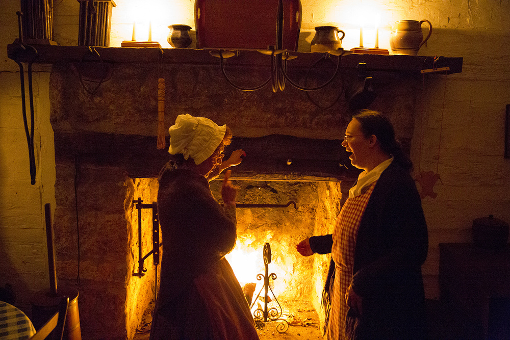 Jane Carrington, left, site interpreter, and Tabby Hyde, a volunteer, visit at the fireplace in the Rutledge Tavern during the annual Candlelight Walk at New Salem State Historic Site Friday, Oct. 2, 2015. Rich Saal/The State Journal-Register