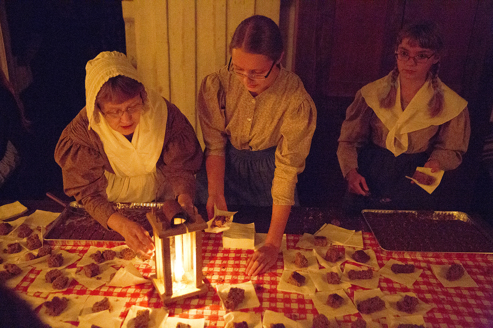 Donna Brantley, left, and sisters Emma and Anna Krumbaugh, served gingerbread in the Rutledge Tavern during the annual Candlelight Walk at New Salem State Historic Site Friday, Oct. 2, 2015. Rich Saal/The State Journal-Register